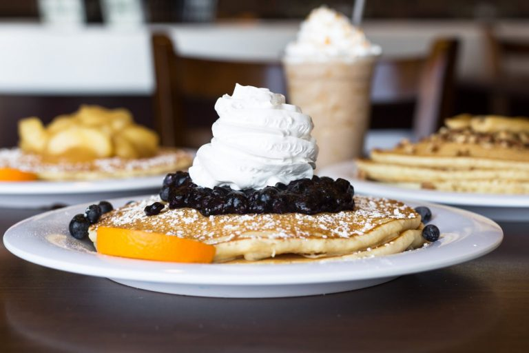 blueberry pancakes on a plate with oranage slice and iced coffee